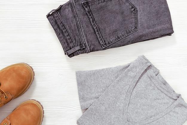 Lay piatto di abiti moda casual donna su stivali bianchi in legno, arancione, jeans neri e maglietta. abbigliamento femminile con spazio di copia.