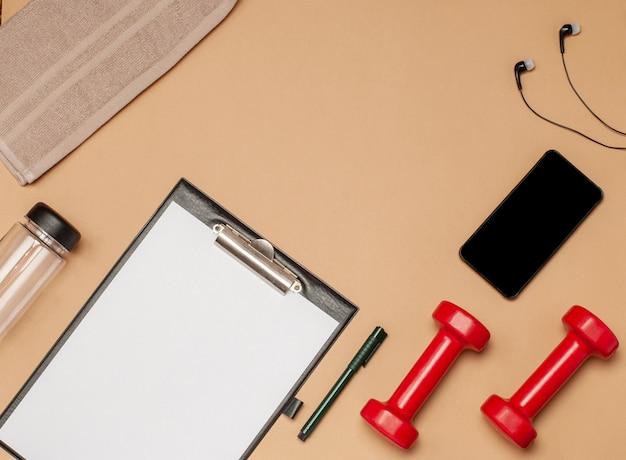 Lay piatto di attrezzature sportive per il fitness su una superficie beige