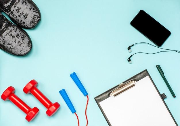 Lay piatto di attrezzature sportive per il fitness su una superficie blu
