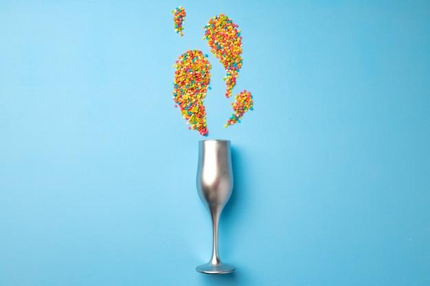 Lay piatto di bicchiere di champagne con coriandoli
