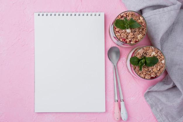Lay piatto di bicchieri di yogurt con cereali e notebook