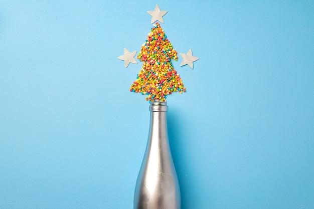 Lay piatto di bottiglia di champagne con coriandoli a forma di albero di natale