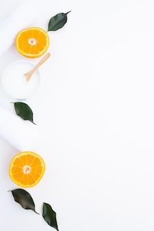 Lay piatto di burro corpo e fette d'arancia con spazio di copia