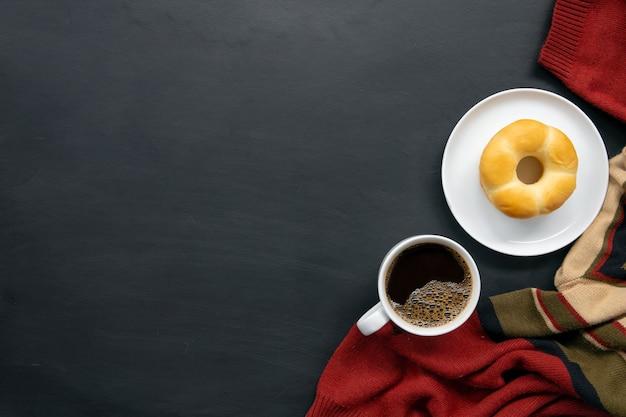 Lay piatto di caffè caldo, maglione e ciambelle