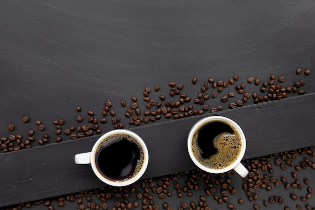 Lay piatto di chicchi di caffè e tazze da caffè