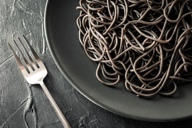 Lay piatto di elegante piastra nera di pasta con inchiostro seppia accanto a una forchetta d'argento con sfondo nero con texture