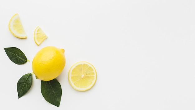 Lay piatto di limone e foglie con spazio di copia