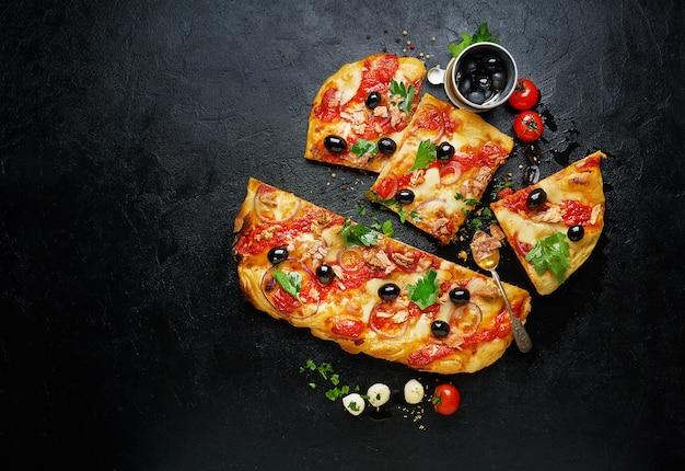 Lay piatto di pizza e ingredienti freschi intorno su sfondo nero. vista dall'alto con spazio di copia