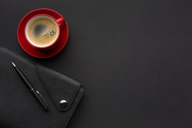 Lay piatto di scrivania con agenda e tazza di caffè