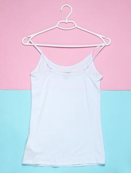 Lay piatto di t-shirt bianca con gancio su sfondo pastello.