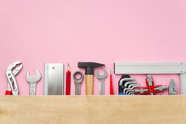 Lay piatto di un set di strumenti per la riparazione domestica su uno sfondo rosa
