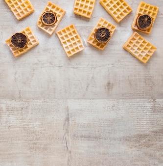 Lay piatto di waffle con agrumi secchi e copia spazio
