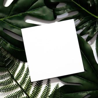 Layout creativo fatto di foglie tropicali con cornice di carta bianca vuota.