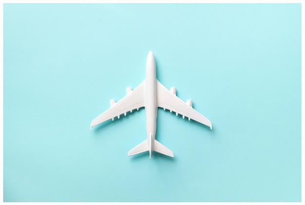 Layout creativo. vista superiore dell'aereo di modello bianco, giocattolo dell'aeroplano su fondo pastello rosa.