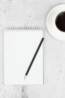 Layout del piano per il giorno. blocco note, matita e tazza di caffè. vista dall'alto