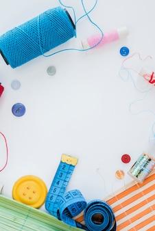 Layout di articoli da cucire sulla scrivania bianca