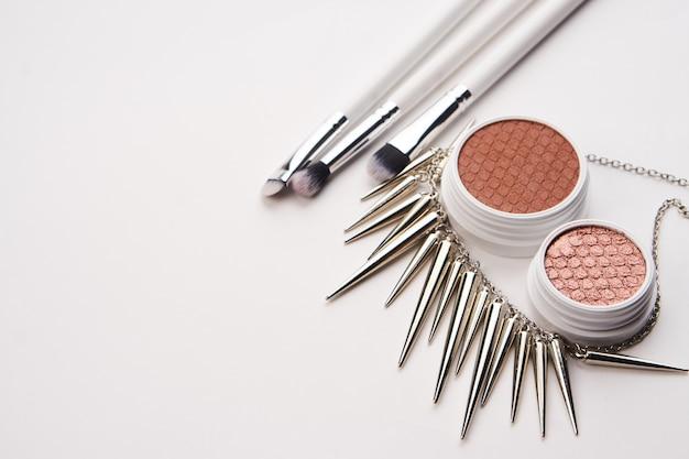 Layout di bellezza su uno sfondo colorato con cosmetici e gioielli