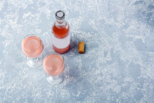 Layout di degustazione di vini rosati. bottiglia aperta e due bicchieri con vino rosato su uno sfondo grigio.