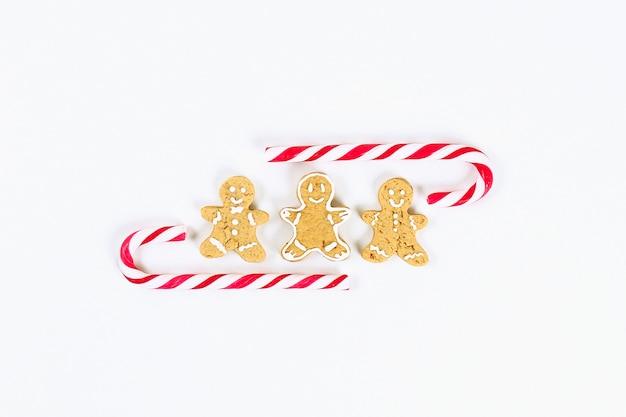 Layout di natale. caramelle di canna rosso-bianco a strisce e biscotti di zenzero fatti in casa su uno sfondo bianco