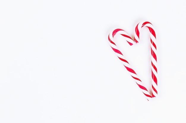Layout di natale. caramelle di canna rosso-bianco a strisce su sfondo bianco. capodanno 2019, natale