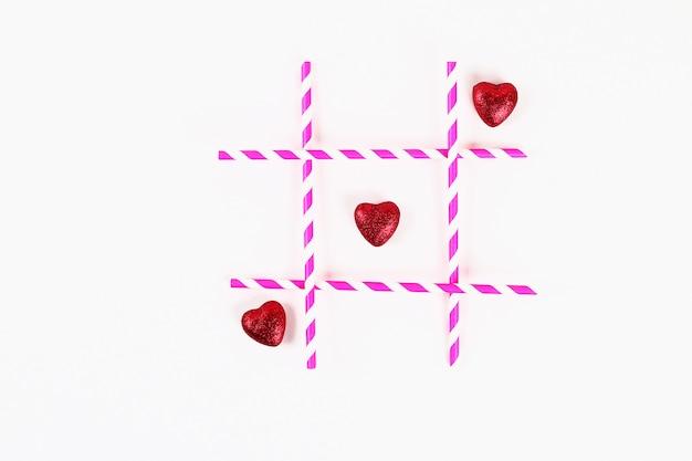 Layout giorno di san valentino. insignificante e croci rosa cannucce e cuori su uno sfondo bianco. tic tac toe.