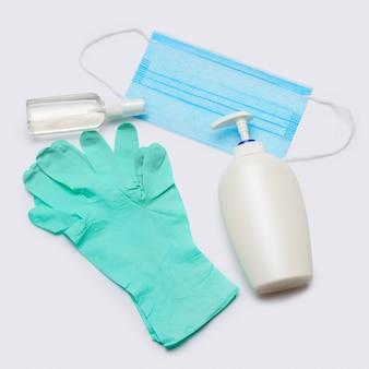 Layout piatto di articoli per l'igiene - guanti in lattice, maschera e disinfettante per le mani su sfondo grigio chiaro