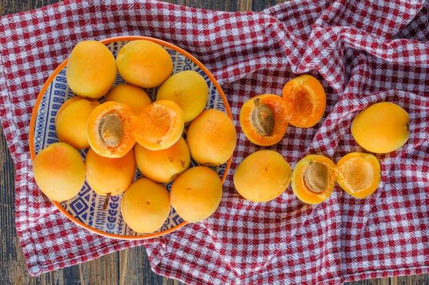 Le albicocche in un piatto piatto giacciono sul panno da picnic e tavolo in legno
