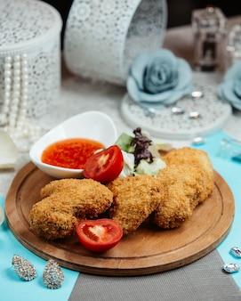 Le ali di pollo fritto croccanti sono servite con lattuga, pomodoro e salsa di peperoncino dolce