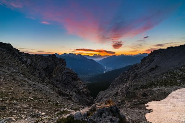 Le alpi all'alba. cielo colorato maestose cime, valli drammatiche, montagne rocciose. vista espansiva dall'alto.