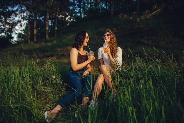 Le amiche emotive si alzano, si siedono sull'erba, bevono cocktail in occhiali da sole in camicia bianca e nera, al tramonto, espressione facciale positiva, all'aperto