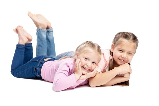 Le amiche in maglioni rosa stanno mentendo e sorridendo. bambini piccoli. isolato su sfondo bianco.