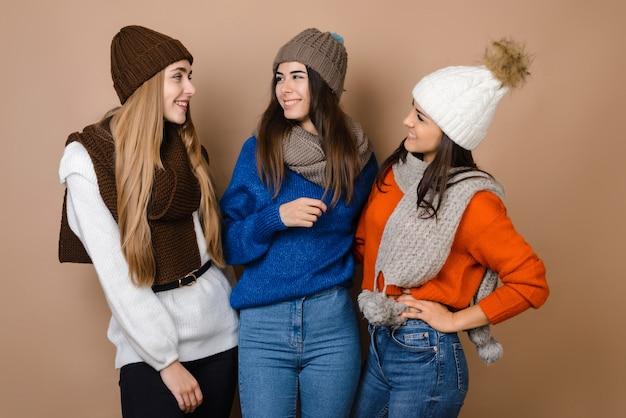 Le amiche posano in caldi cappelli e sciarpe