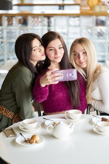 Le amiche si divertono nel caffè, bevono tè e fanno selfie