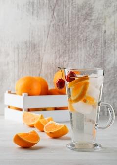 Le arance in una scatola di legno con frutta hanno infuso la vista laterale dell'acqua sulla superficie bianca