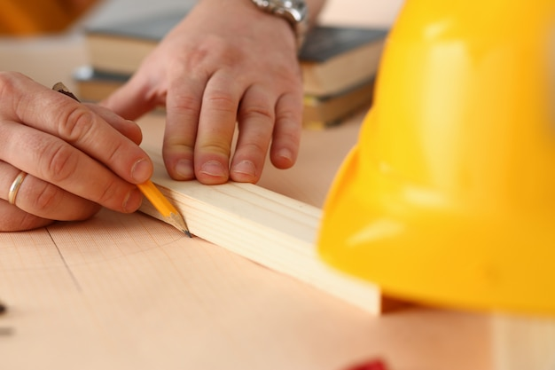 Le armi del lavoratore che fanno la struttura progettano sul primo piano di carta riportato in scala. lavoro manuale ispirazione fai-da-te miglioramento lavoro negozio grafico falegnameria avvio sul posto di lavoro idea designer carriera educazione industriale