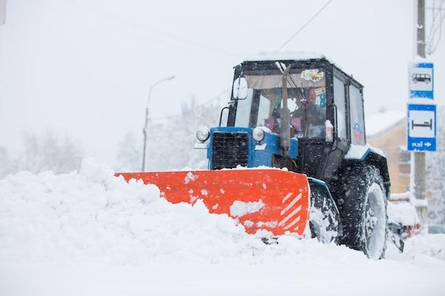 Le attrezzature di servizio puliscono la neve per le strade