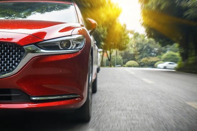 Le auto attraversano la foresta dalla strada asfaltata