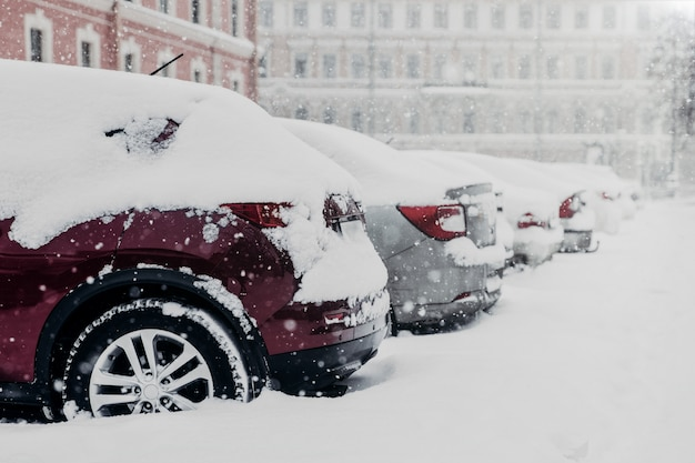 Le auto parcheggiate sono bloccate nella neve dopo una forte tempesta di neve al parcheggio