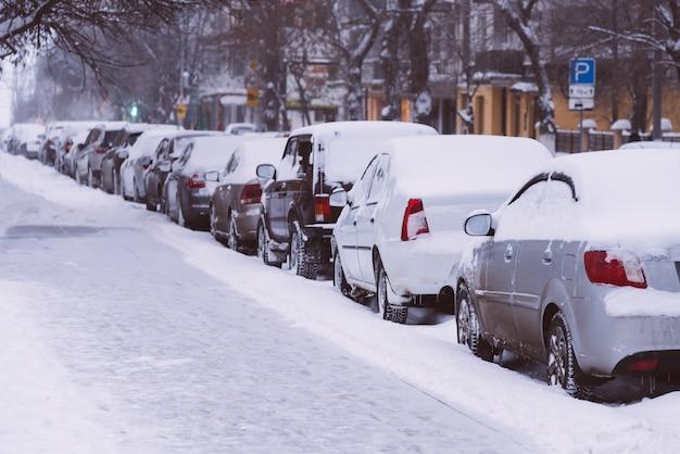 Le auto sono parcheggiate lungo le strade coperte di neve