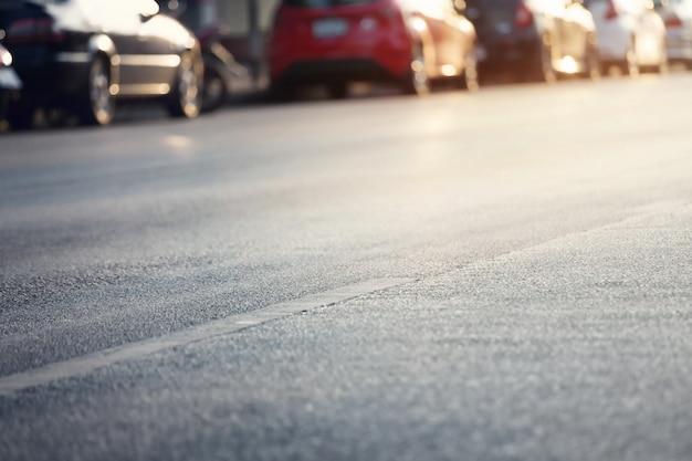 Le automobili hanno parcheggiato sulla via in città nel giorno di estate soleggiato.