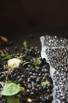 Le bacche di chokeberry (aronia melanocarpa) sono confezionate in sacchetti sottovuoto e bacche nere sul tavolo scuro.
