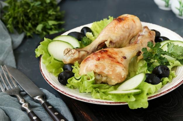 Le bacchette di pollo sono servite con cetrioli, olive nere e lattuga su un piatto