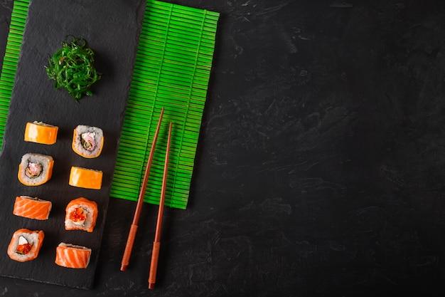 Le bacchette giapponesi dei sushi sopra la ciotola della salsa di soia, riso su fondo di pietra nero. vista dall'alto con lo spazio della copia
