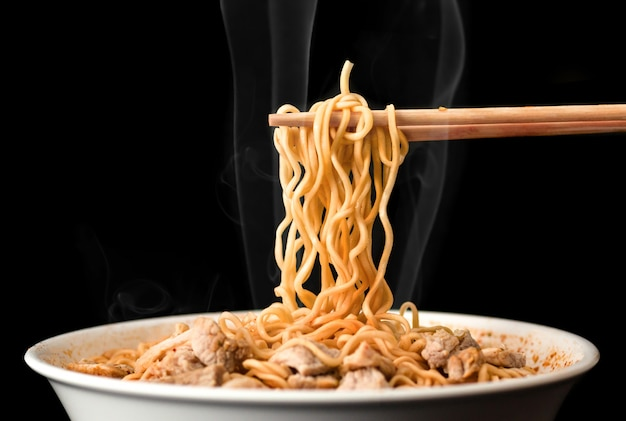 Le bacchette raccolgono gustosi spaghetti con fumo su sfondo scuro. ramen in una ciotola bianca.
