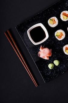Le bacchette si avvicinano al piatto del raccolto con i sushi