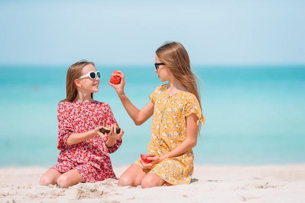 Le bambine divertenti felici si divertono molto in spiaggia tropicale giocando insieme