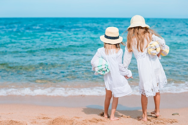 Le bambine divertenti felici si divertono molto in spiaggia tropicale giocando insieme.