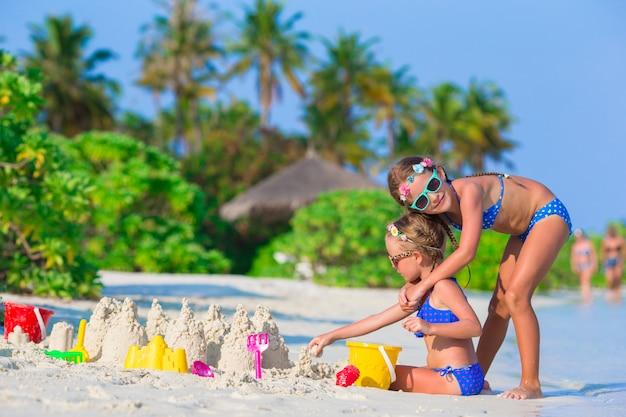 Le bambine felici che giocano con la spiaggia giocano durante la vacanza tropicale