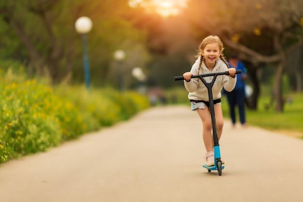 Le bambine si divertono con il suo scooter nel parco