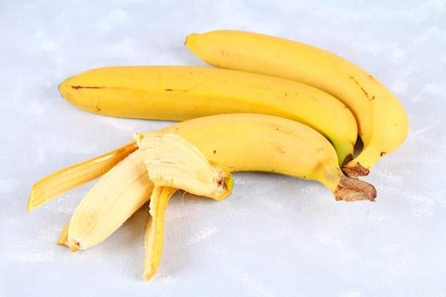 Le banane sono intere e tagliate su una fetta in una tazza su uno sfondo grigio